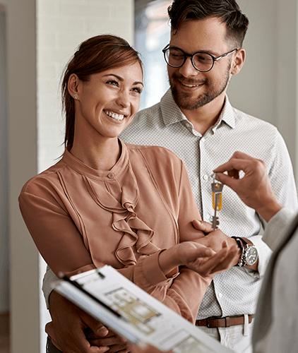 Imagen de pareja recibiendo llaves de casa- crédito para casa y terreno